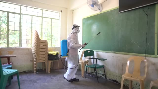 local government workers wear hazmat suits as they disinfect and sanitize a public school building as a precautionary measure against coronavirus in... - philippines stock videos & royalty-free footage