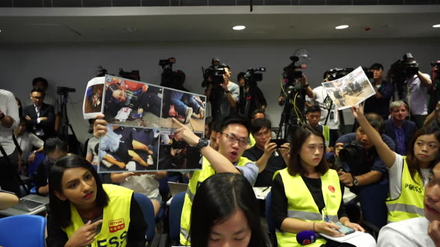 local journalists at police press conference hold up photos of antigovernment protesters allegedly injured by the police in hong kong - hong kong stock videos & royalty-free footage