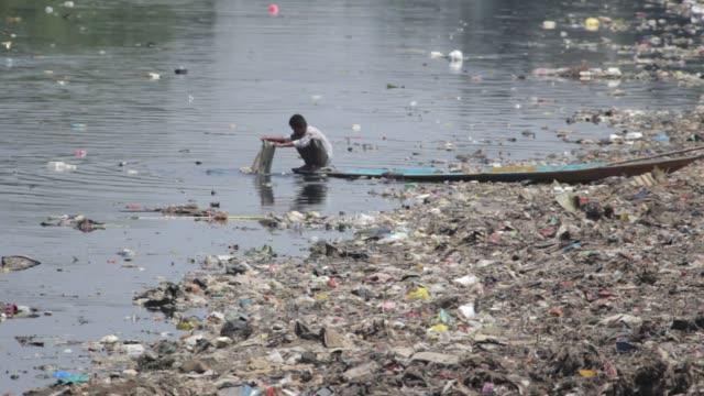 vídeos y material grabado en eventos de stock de local man soaks a piece of cloth in the river citarum. - yakarta