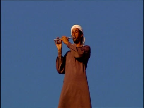 local man wearing robe and turban plays pipe against blue sky petra jordan - turban stock videos & royalty-free footage