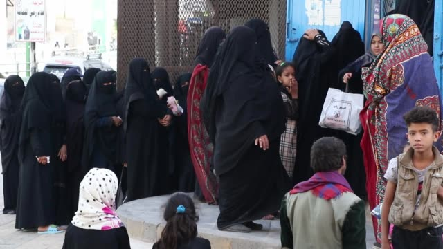 vídeos de stock, filmes e b-roll de local people affected by the yemen conflict wait to receive bread as aid provided by a local charity center on april 04 2019 in sana'a yemen un... - the center