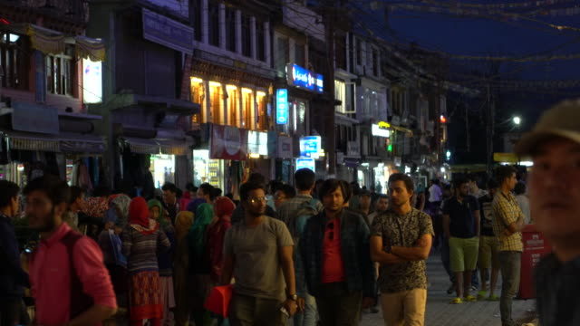 vidéos et rushes de local people and tourist walk on the central very busy street in leh, ladakh in the evening - inde