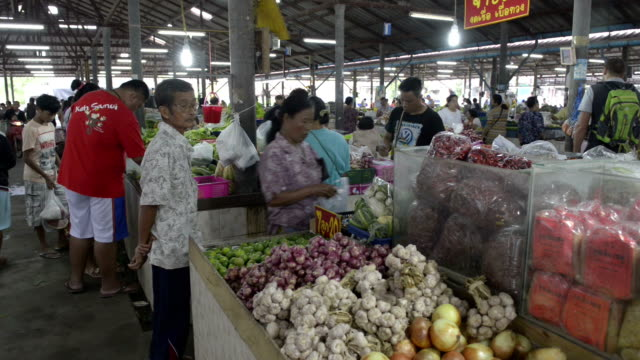 Local people in a covered market with garlic stall