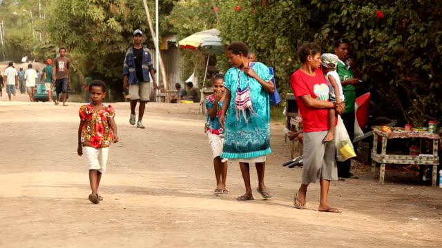 Local people walking down street in rural village Papua New Guinea is an island located in Oceania There are around 850 languages spoken on the...