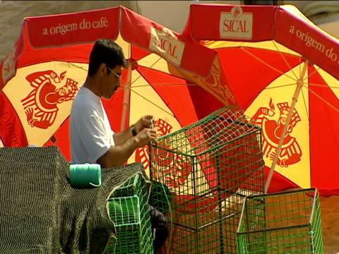 vídeos de stock, filmes e b-roll de local portuguese man ties string around fishing basket shaded by colorful sun umbrellas fisherman's beach - indústria da pesca