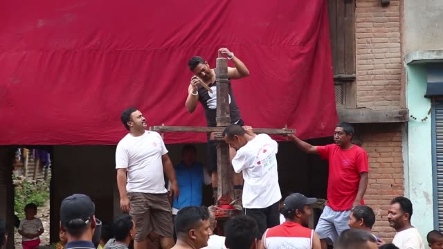 local residents from newar community prepare a chariot with the balanced children above a prong planted to mark trishul jatra festival in kathmandu... - balance stock videos & royalty-free footage