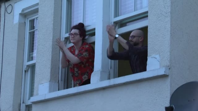 local residents outside st george's hospital, in the tooting area of london, and police officers in falkirk, in scotland, applaud medical workers... - clapping hands stock videos & royalty-free footage