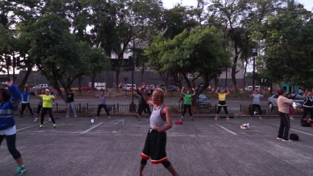 Local residents take part in a Zumba exercise routine near Manila Bay in Manila the Philippines on Friday May 22 People jog along a road near the...