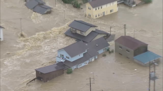 local residents wave to call rescueas the area is submerged while damages caused by floodwater and landslide are seen in kurashiki okayama prefecture... - 自然災害点の映像素材/bロール