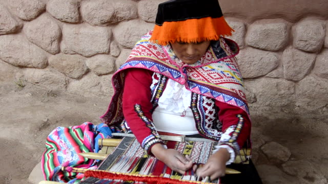 MS Local sitting woman in traditional clothes weaving yarn / Sacred Valley, Peru