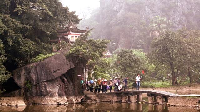 Local tourists crossing bridge from temple Tam Coc nr Ninh Binh nr Hanoi Asia