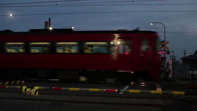 local train passing at dusk - level crossing stock videos & royalty-free footage