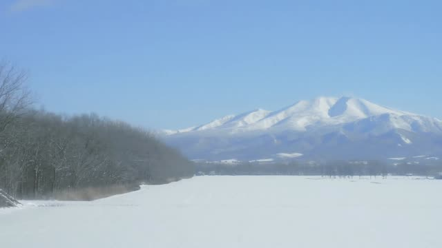 Local train passing snow covered wilderness in Hokkaido, Japan