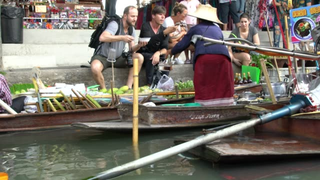 local vendor at damnoen saduak floating market not far from bangkok, thailand - tourist stock-videos und b-roll-filmmaterial