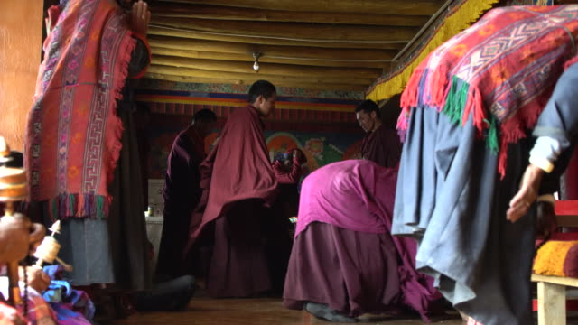 Local villagers wearing traditional Ladakhi clothing praying in the main praying room of the Korzok Tibetan Buddhist monastery, Ladakh, India