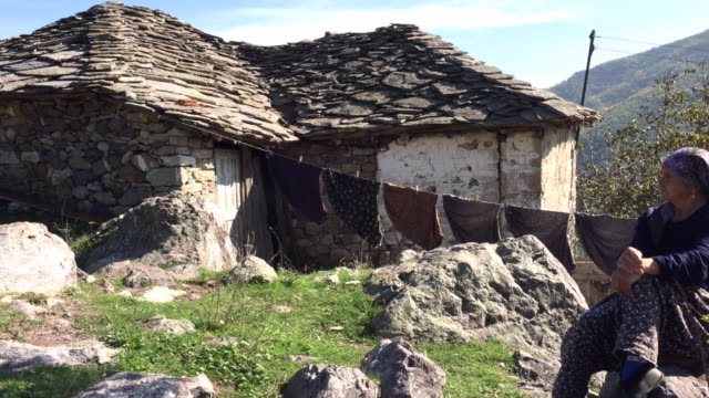 local woman from pomak ethnicity nearby her old house in the village of bezvodno, rhodope mountains, bulgaria - macedonia country stock videos and b-roll footage