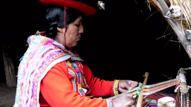 MS Local woman sitting in traditional clothes weaving yarn / Sacred Valley, Peru