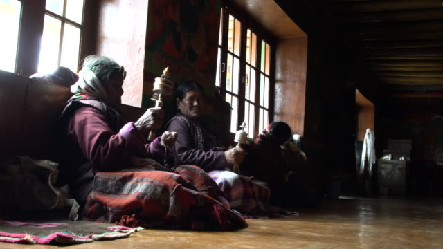 Local women spinning her buddhist prayer wheel in main praying room of the Korzok Tibetan Buddhist monastery, Ladakh, India