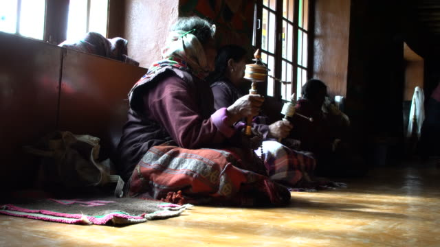local women spinning her buddhist prayer wheel in main praying room of the korzok tibetan buddhist monastery, ladakh, india - traditionally tibetan stock videos & royalty-free footage