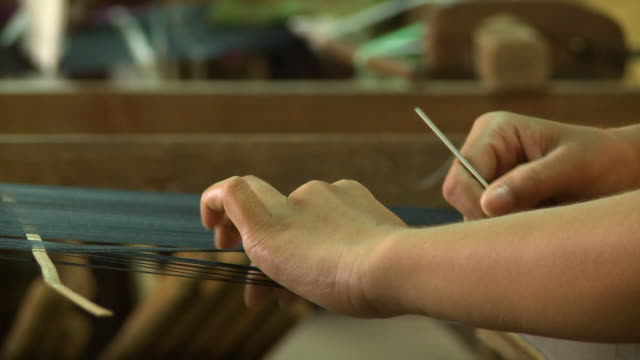 a local worker sorting black silk threads by hand - loom stock videos & royalty-free footage