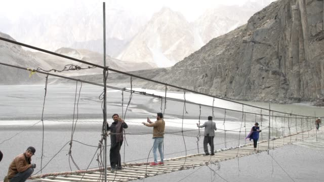 locals and tourist trying to walk on hussaini suspension bridge, over the hunza river, hunza, pakistan - electrical component stock videos & royalty-free footage