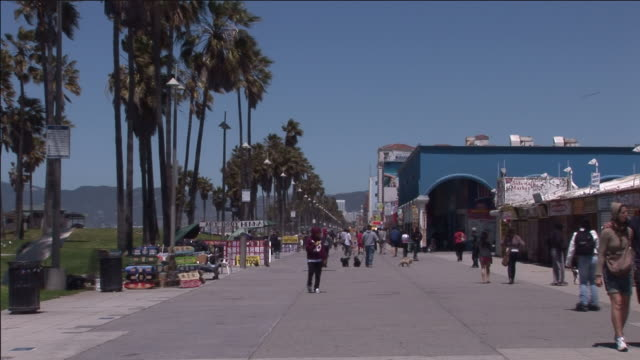 locals and tourists move along a sidewalk in marina del rey. - blade stock videos & royalty-free footage