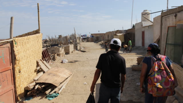 Locals are walking between self made huts in a dry and sandy village in a Slum of Tortuga Peru