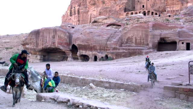 vídeos de stock e filmes b-roll de locals from petra riding their donkeys early in the morning, jordan - petra