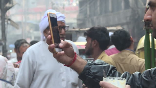 Locals on mobile phones at busy street market in India