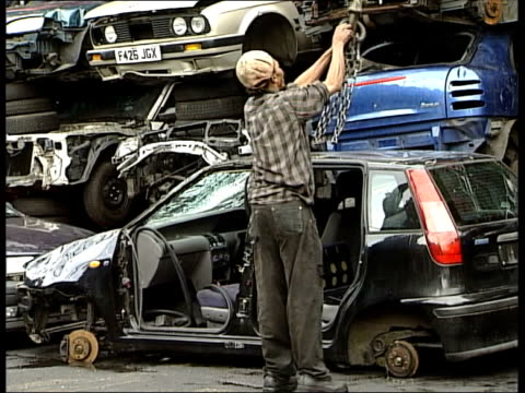 stockvideo's en b-roll-footage met bv scrapyard worker attaching car to crane hoist - hijsen