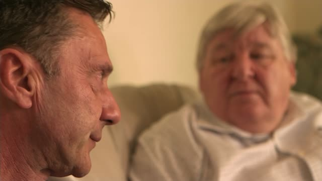 EXT Richard Kerr along to house Kerr knocks on door Brian Gemmell opens door and they greet and shake hands NATSOT Shots of Richard and Brian sitting...