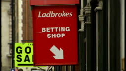 Signs showing Ladbrokes betting shop and Northern Rock bank Stock Footage  Video