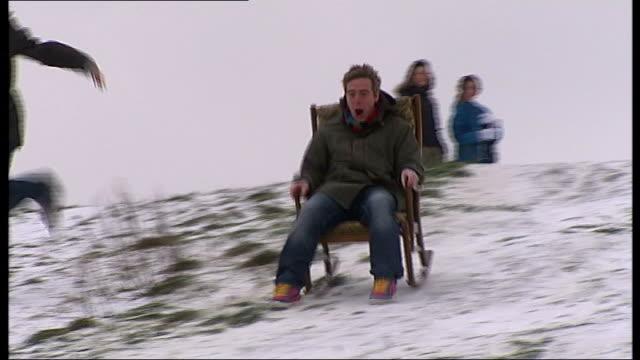 man sledging down hill on rocking chair - dondolarsi video stock e b–roll