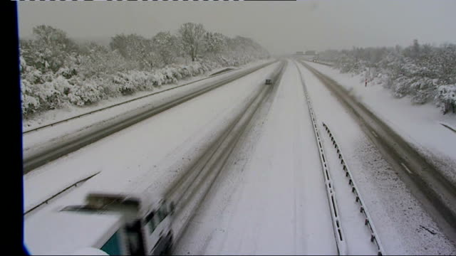 gritter truck with snowplough attachment along through slush traffic along on snow-covered motorway int baroness eaton interview sot - baroness stock videos & royalty-free footage