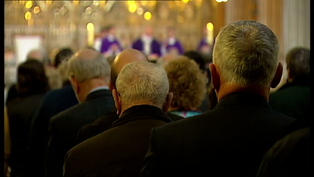 hands holding rosary congregation and priests on altar in background nuns in congregation lit candle - worry beads stock videos & royalty-free footage