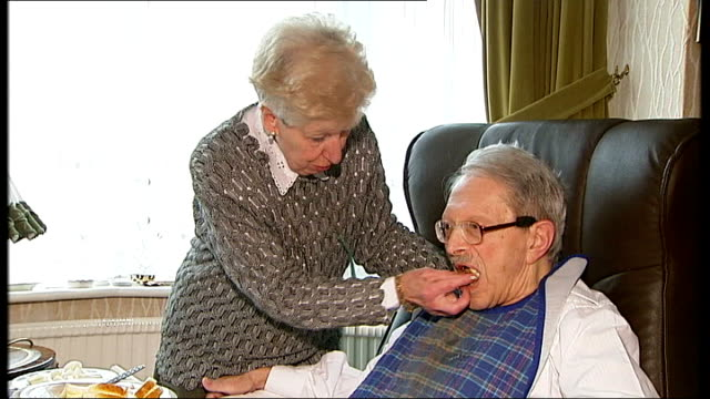 stockvideo's en b-roll-footage met int retired couple sheila and sid penfield at home as sheila feeds ted carer moving hoist out of room sheila talking to and cleaning up sid sheila... - hijsen
