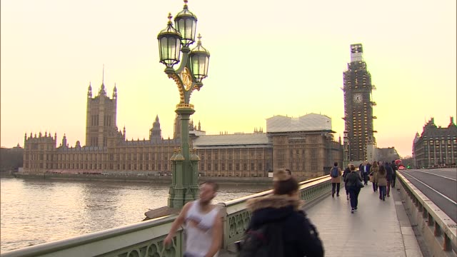 general views of london westminster gvs pedestrians commuters england london ext gvs people crossing westminster bridge / parliament with people past... - westminster bridge stock-videos und b-roll-filmmaterial