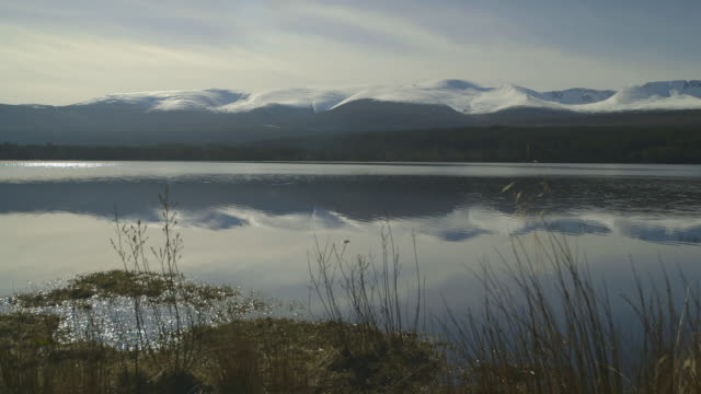loch and snow capped cairngorm mountains, scotland - スコットランド点の映像素材/bロール