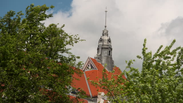 lockdown: a beautiful tile roof and limestone spire above trees - kirchturmspitze stock-videos und b-roll-filmmaterial