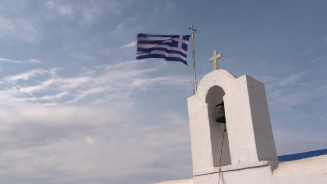 lockdown: a greek flag flies above a lovely church bell tower in naoussa - greek flag stock videos & royalty-free footage