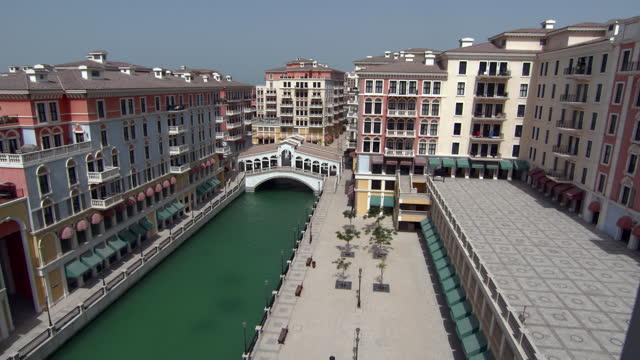 lockdown: a green canal runs through a gorgeous sunny courtyard with mediterranean style buildings in the sun - doha, qatar - qatar stock videos & royalty-free footage
