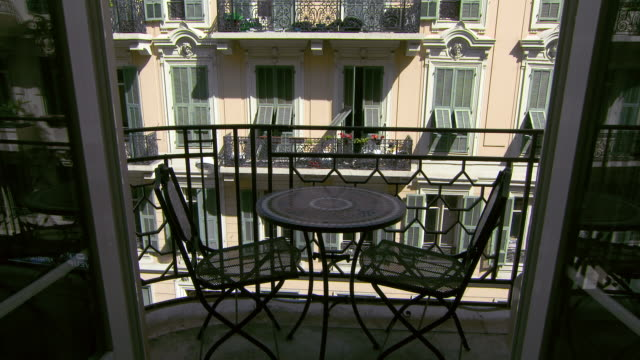 lockdown: balcony table and chairs with a view of the opposing architecture - patio stock videos & royalty-free footage