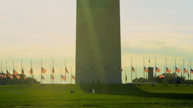 lockdown: base of washington monument with flags (shot on red) - washington monument washington dc stock videos & royalty-free footage