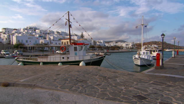 vídeos de stock, filmes e b-roll de lockdown: beautiful yachts docked at a pier by beautiful naoussa village - píer