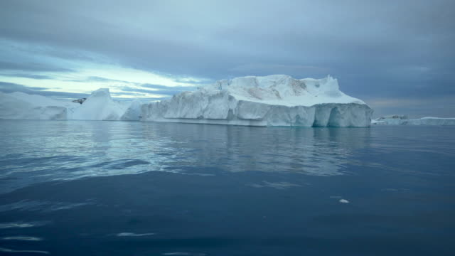 lockdown: big iceberg in the cold waters of greenland disko bay - weathered stock videos & royalty-free footage