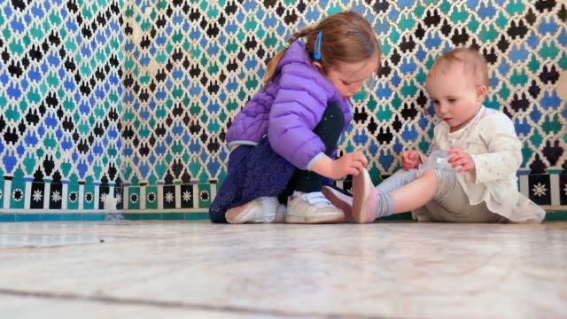 lockdown: big sister helping little sister put on shoe - other点の映像素材/bロール
