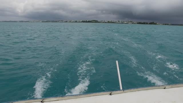 lockdown: boat speeding away from island of hamilton bermuda in hamilton, bermuda - bermuda stock videos & royalty-free footage