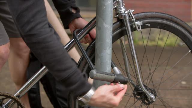 vídeos y material grabado en eventos de stock de lockdown close-up of male commuter unlocking bicycle from wet rack - cerradura
