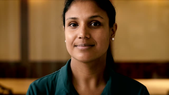 vidéos et rushes de lockdown close-up shot of confident businesswoman smiling in office - indien d'inde