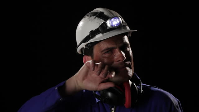 cu, lockdown, coal miner removing hardhat and wiping sweat off his upper lip - minatore video stock e b–roll